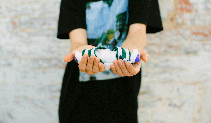 Image shows two hands holding a piece of wrap art.