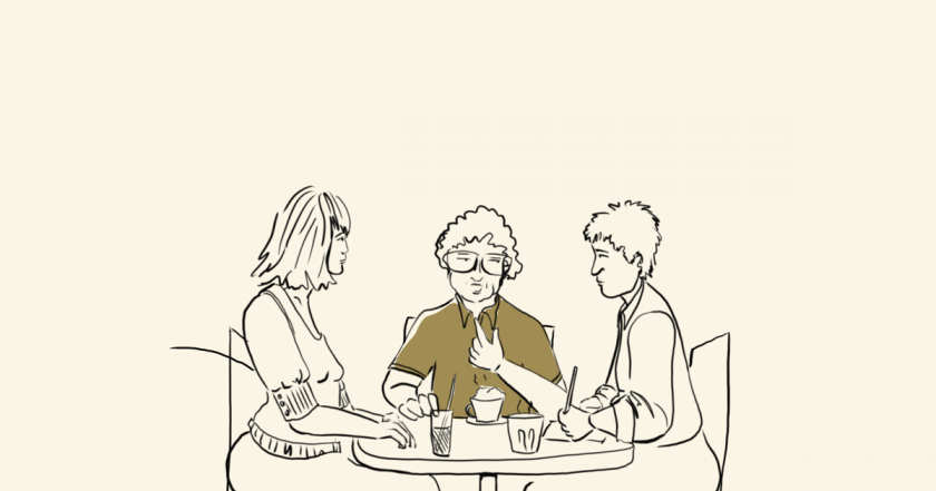 Three people talking in a café.